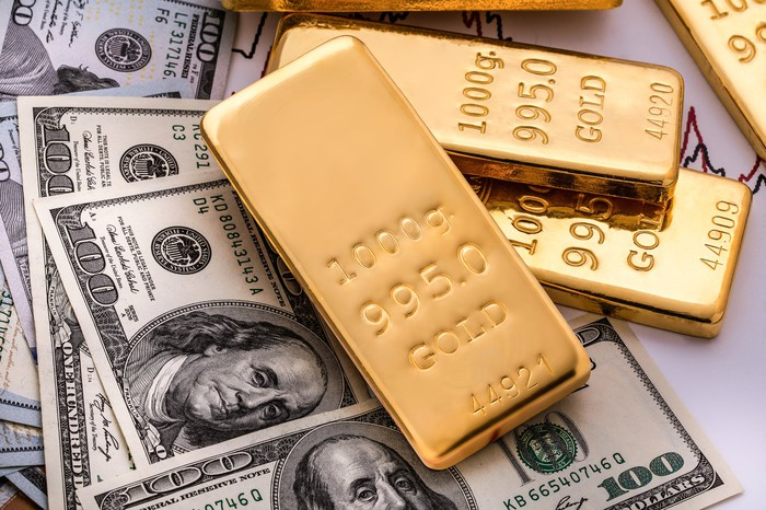 Gold ingots are scattered atop hundred-dollar bills.