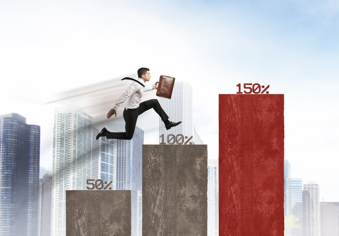 A man jumping up columns with different percentages on top