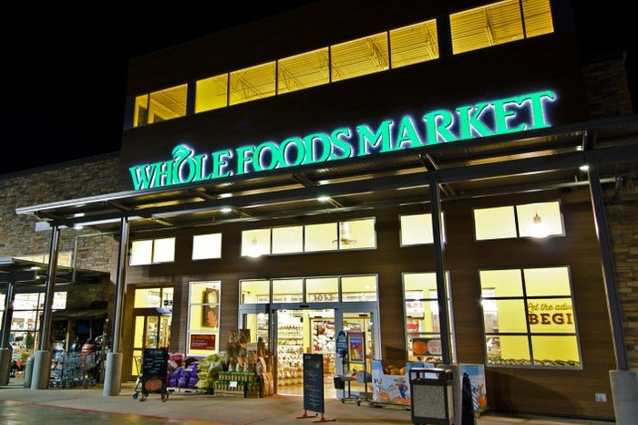 The entrance of a Whole Foods store lit up at night