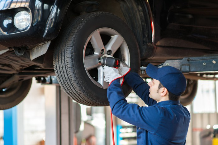 A mechanic replacing a car wheel.