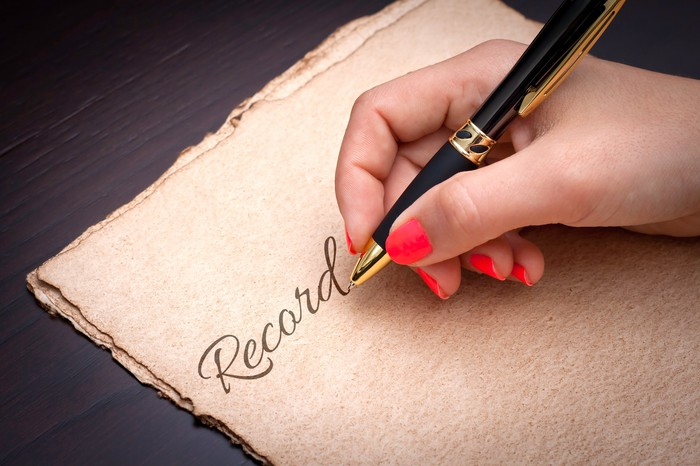 """Woman writing """"Record"""" on a sheet of papyrus."""