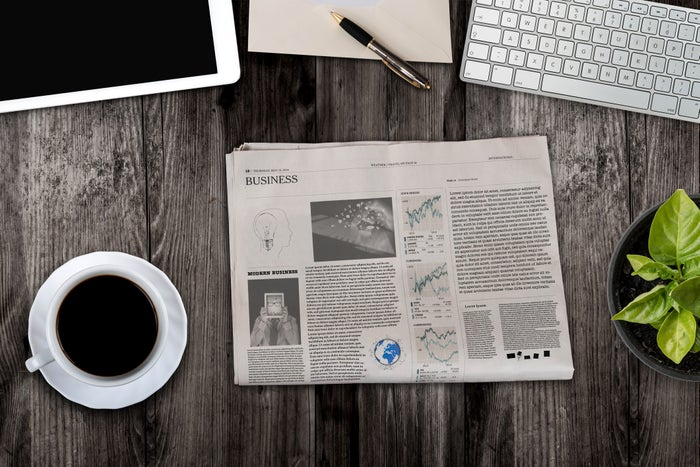Newspaper on a table next to a cup of coffee, a tablet, a keyboard, and a notebook
