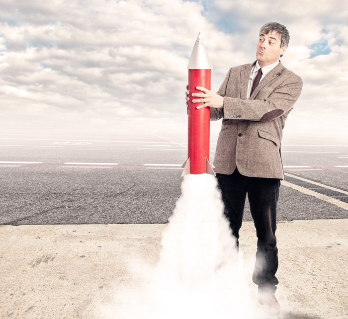 Man with surprised look on his face, holding a toy rocket that's about to take off.