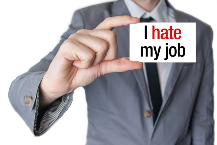 "Man holding card stating ""I hate my job"""
