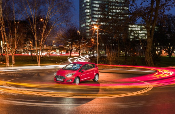 A red Ford Fiesta parked against a nighttime urban backdrop.