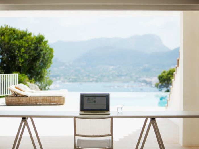 A laptop on a table with a background view of a waterfront