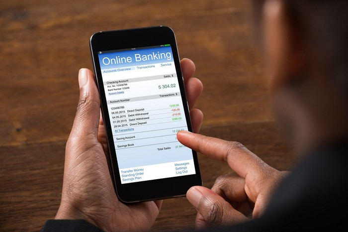 Woman using online banking app on smartphone.