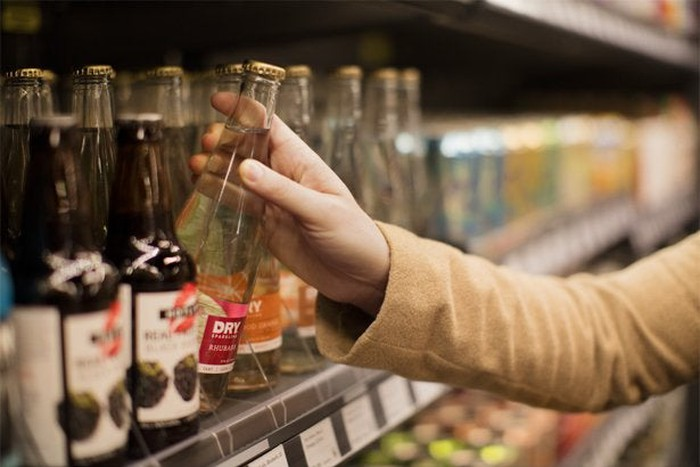 A person selects an bottle from a store shelf.