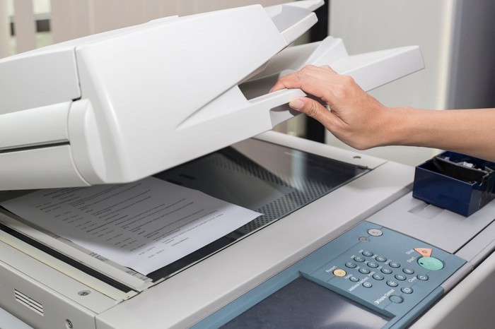 A hand lifting the cover of a photocopier.