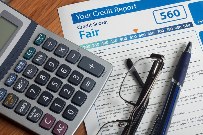 A credit report, with a score of 560, sits on a table with a pen, glasses, and calculator.