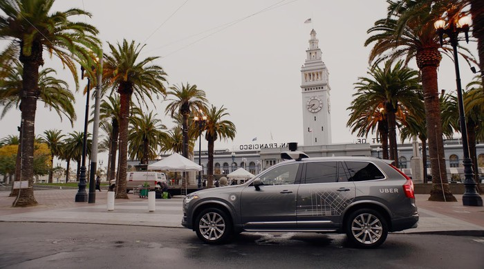 A Volvo SUV with Uber logos and self-driving sensors on a street in San Francisco