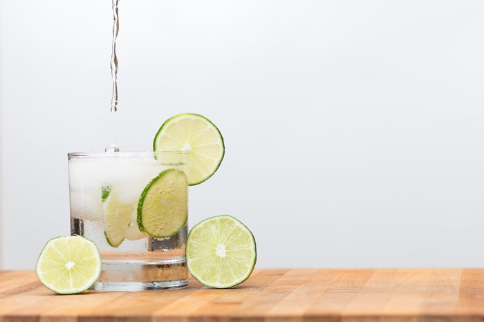 Sparkling water being pored into a glass with limes.