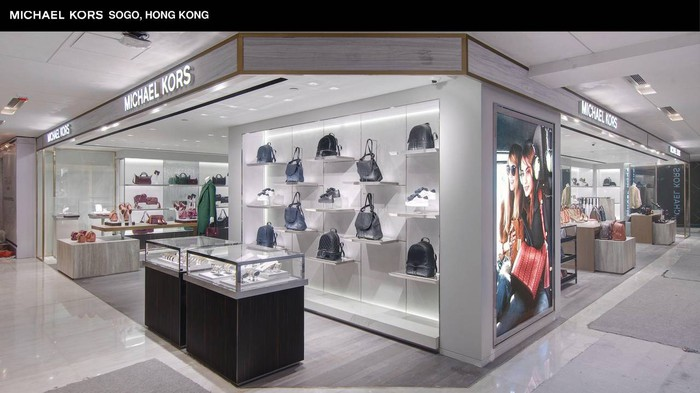 A Michael Kors storefront showing a display of handbags