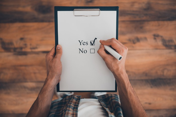 "Man checking off ""yes"" on a yes or no checklist."