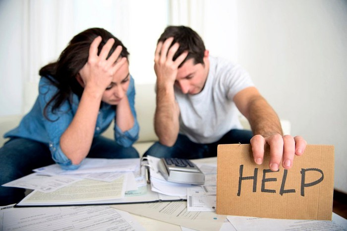 "A frustrated couple, hands grasping heads, look over a pile of bills, with the man holding a sign that reads ""help."""