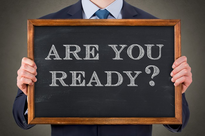 "A man in a suit holds a blackboard that says ""Are you ready?"""