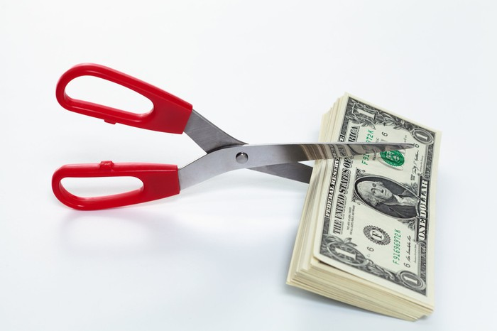 A pair of scissors are set to cut a stack of dollar bills.