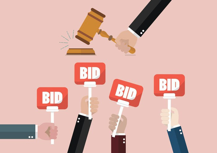 "Vector illustration of hands holding up signs labeled ""Bid"" as a gavel comes down."