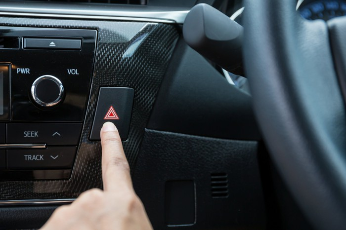 A driver reaches for the hazard-light switch on the dashboard.