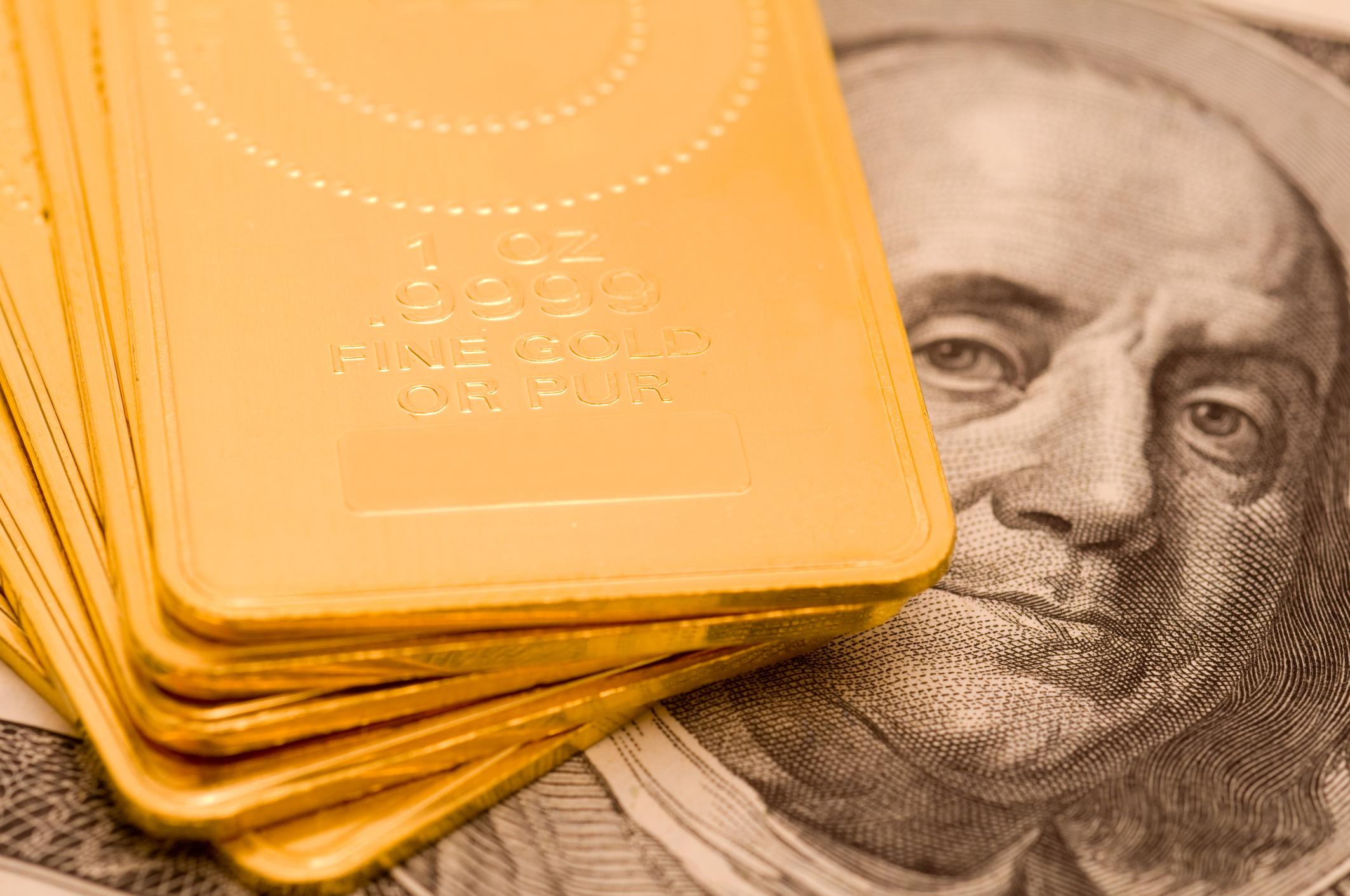 Gold ingots lying atop a hundred dollar bill.