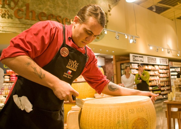 A Whole Foods employee slices a wheel of cheese.