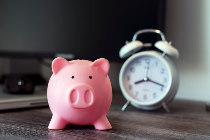 A piggy bank with a clock in the background