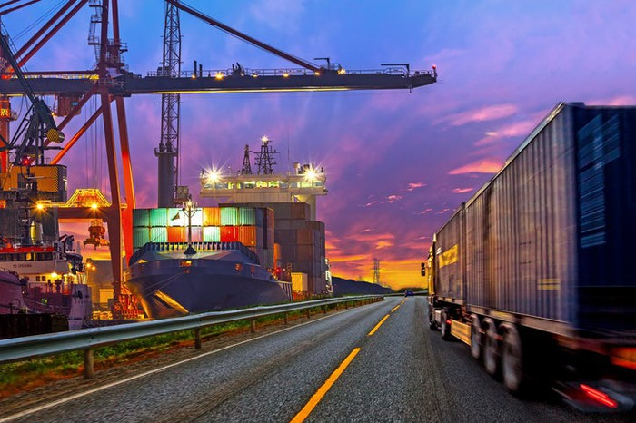 Freight truck driving beside container docks near dusk.