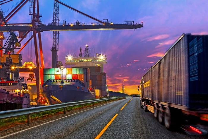 Freight truck driving beside container docks near dusk.