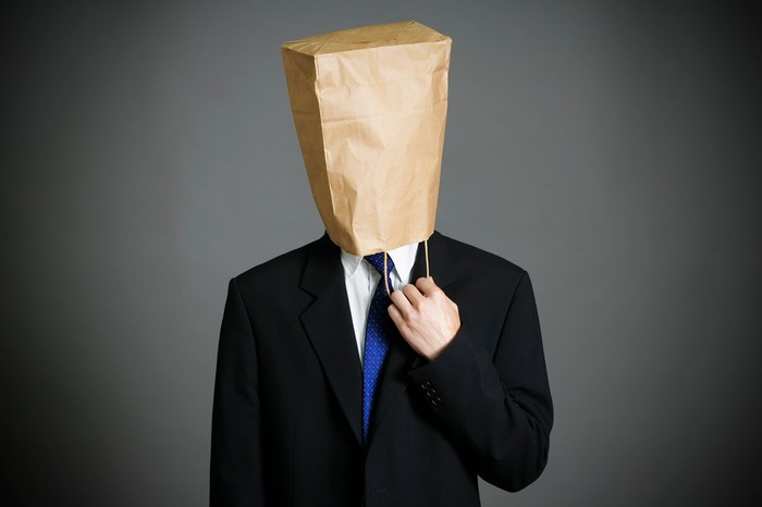 A businessman with a bag on his head.