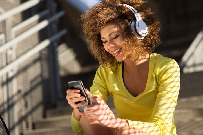 A women using a phone and listening to wireless headphones.
