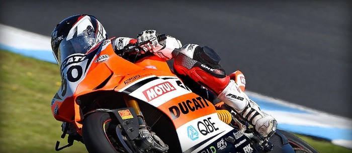A racer on the track makes a turn on a Ducati racing motorcycle.