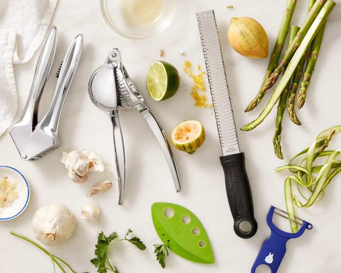Various utensils and chopped-up ingredients on a white countertop