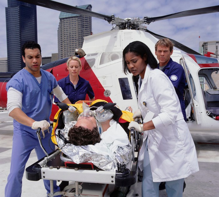 Medical professionals transporting patient from emergency medical helicopter.