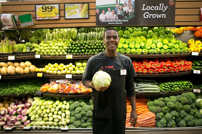 A Kroger employee holding a head of cabbage in the produce aisle.