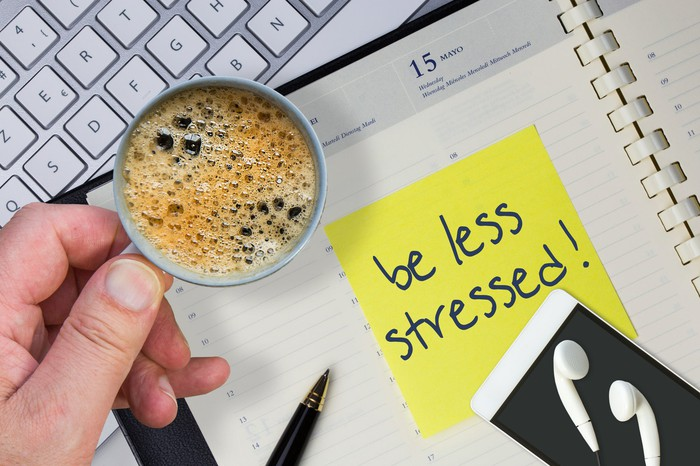 "A scattered desk with a note saying ""be less stressed!"""