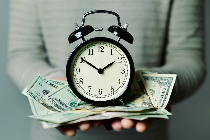 An old fashioned clock sits on top of a pile of money in someone's hands.