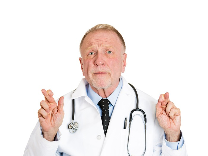 A doctor crossing his fingers.