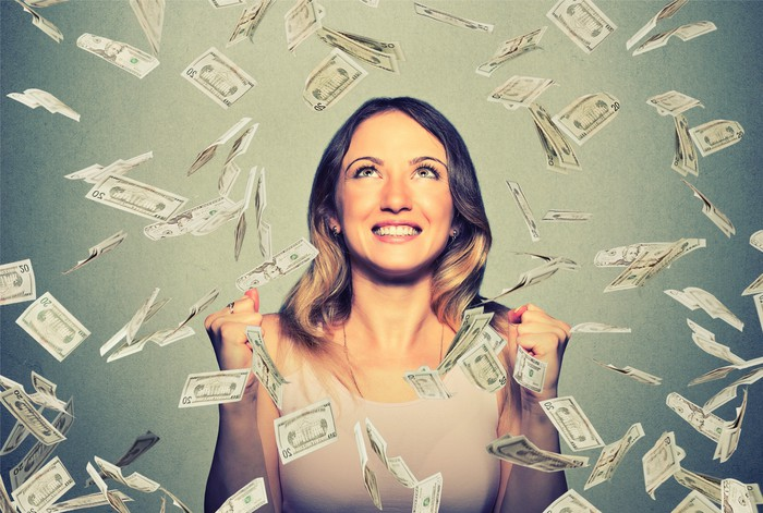 A woman stands in a shower of cash.