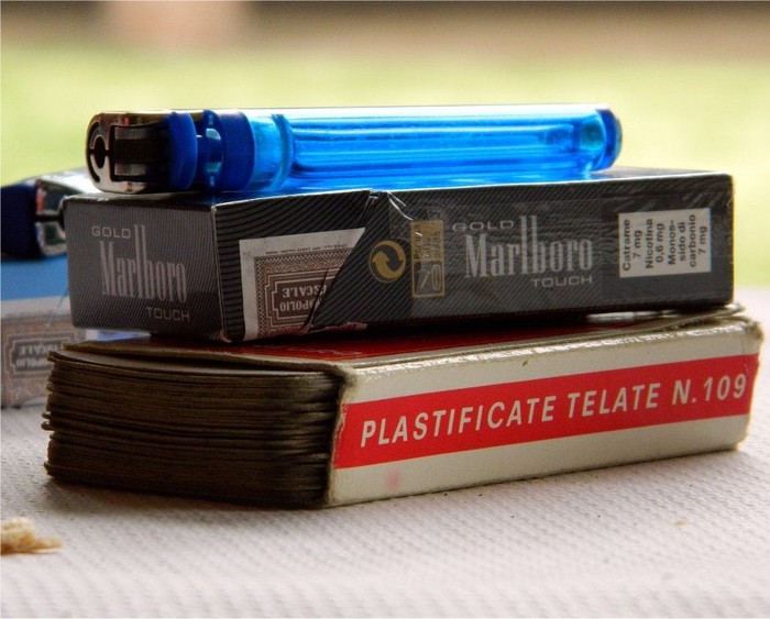 A lighter, pack of Marlboro cigarettes, and playing cards.