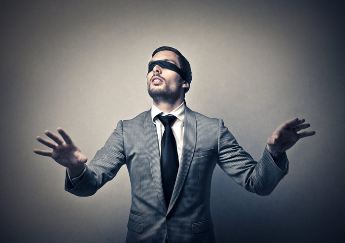 A man in a business suit wearing a blindfold