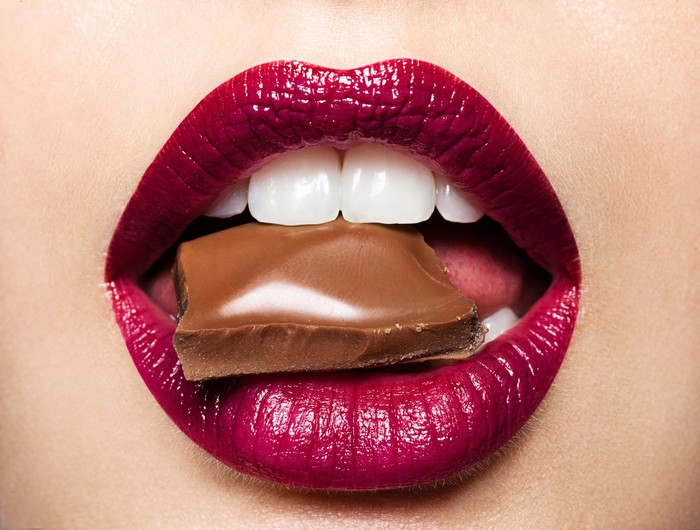 Piece of milk chocolate in woman's mouth.