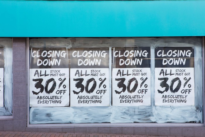 Retail storefront with going-out-of-business posters in window.