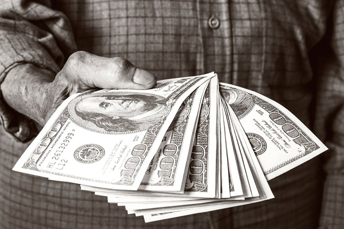 A senior holding a stack of Social Security cash.