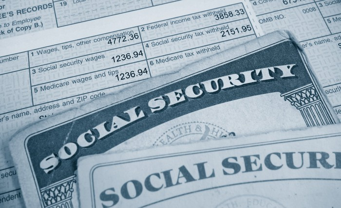 Social Security cards atop a paycheck, highlighting payroll taxes taken out.