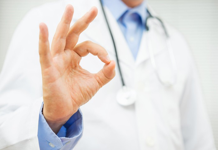A doctor makes an OK symbol with his hand.