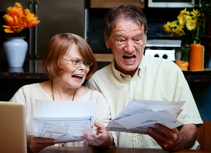 An older couple looks at a handful of papers with an alarmed expression.