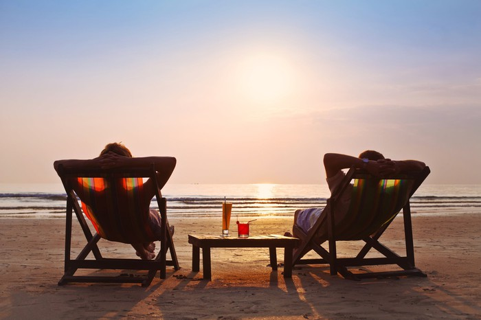 Two people on beach chairs at beach as sun sets