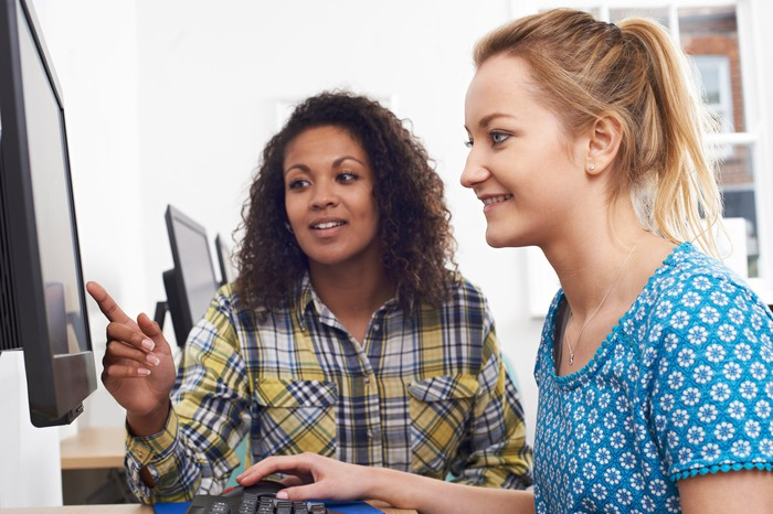 Two women looking camera left at a computer screen