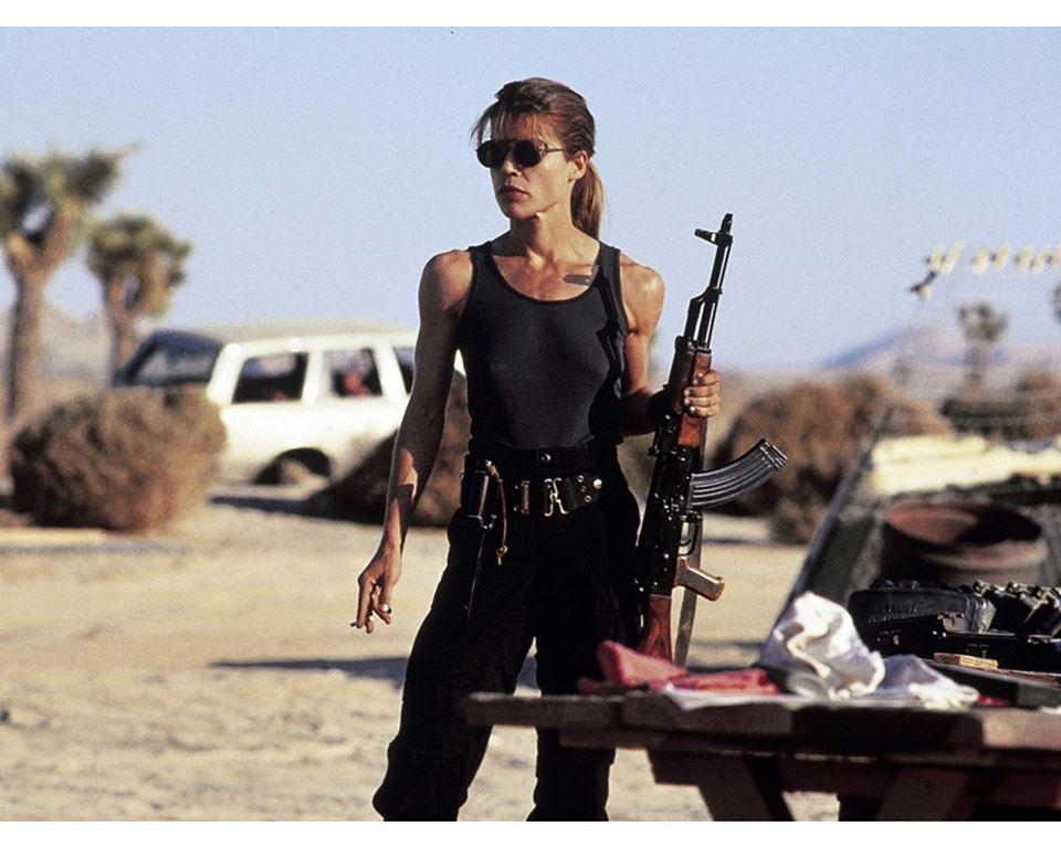 Actress Lilnda Hamilton portraying Sarah Connor, holding a gun in a desert.