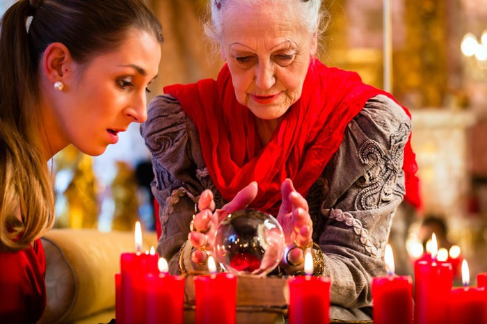 Two women: elderly soothsayer with crystal ball, and young client looking surprised.